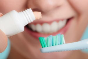 Dental health care. Closeup woman holding toothbrush and placing toothpaste on it smiling face in the background